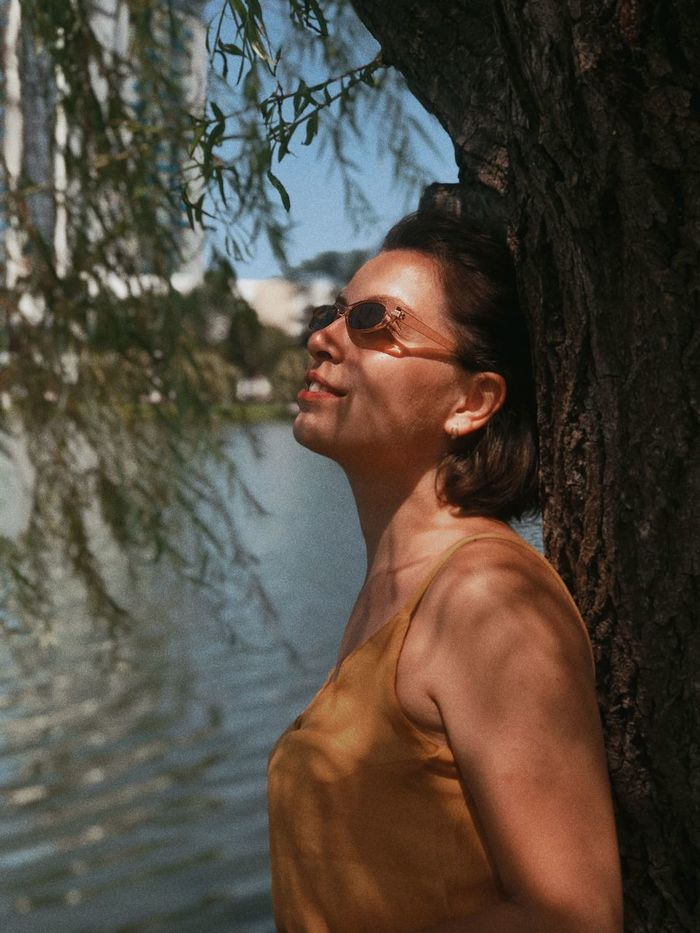 Side view of smiling young woman wearing sunglasses standing by tree