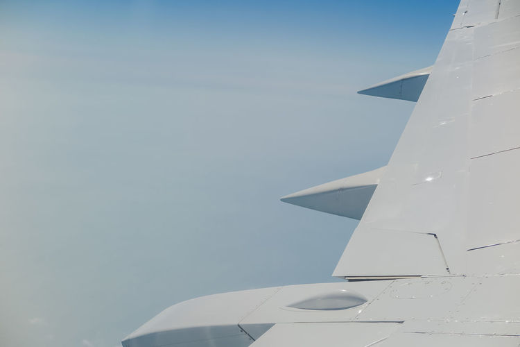 view of the wing of the aircraft in flight in the clouds Air Vehicle Airplane Sky Mode Of Transportation No People Aircraft Wing Transportation Flying Nature Day Travel Mid-air Outdoors Clear Sky Motion Copy Space Vehicle Part on the move Blue Aerospace Industry