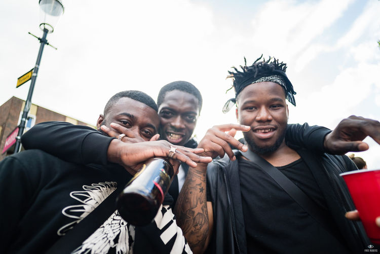 Notting Hill Carnival 2016 Casual Clothing Cloud - Sky Friendship Front View Headshot Holding Leisure Activity Lifestyles Looking At Camera Medium Group Of People Person Sky Standing Togetherness Toothy Smile Warm Clothing Young Adult Young Men