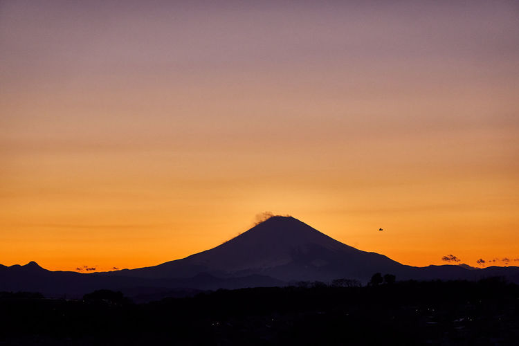 Scenic view of silhouette mountains and a bird against sky during sunset