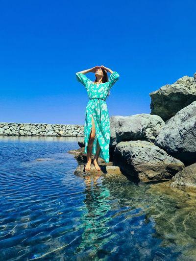 Full length of woman standing on rock against blue sky