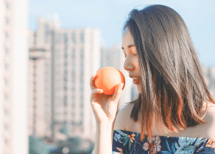 Woman holding orange in city