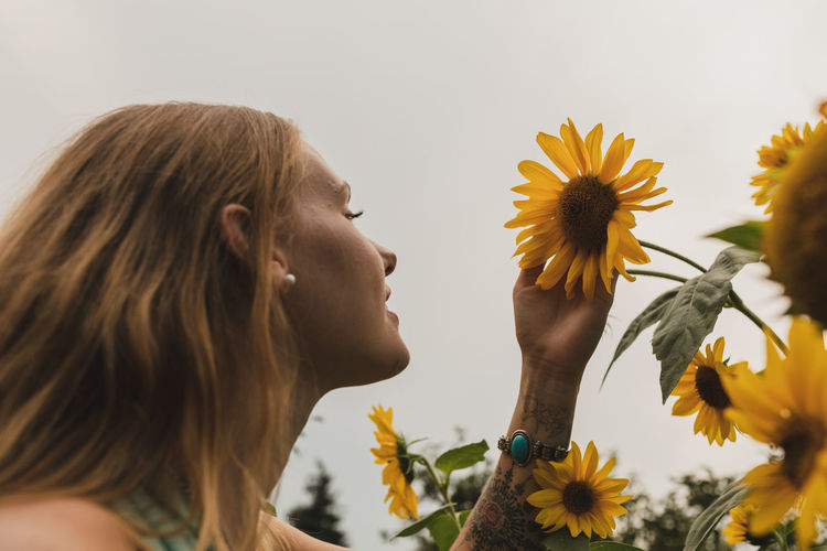 Low angle view of woman looking at flower against sky