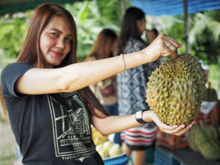 Portrait of smiling woman holding durian