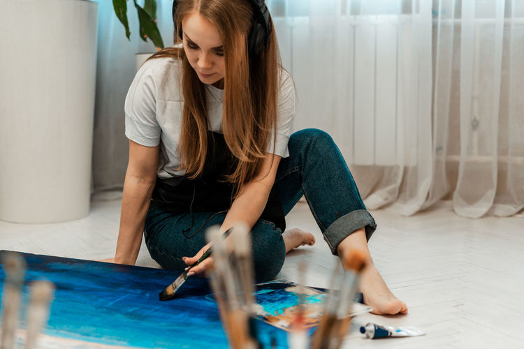 Woman painting on canvas while sitting at home