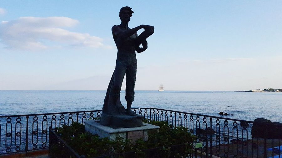 Statue in Giardini Naxos . around the beach . a roadtrip to Sicily . September 2018 . Giardininaxos Roadtrip Statue Statues And Monuments Water Military Sea Men Full Length Statue Standing Silhouette Sky Horizon Over Water Sculpture Warrior - Person Sculpted Knight - Person Suit Of Armor Male Likeness Shield Archery