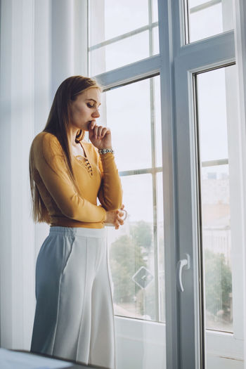 Young woman looking away while standing on window