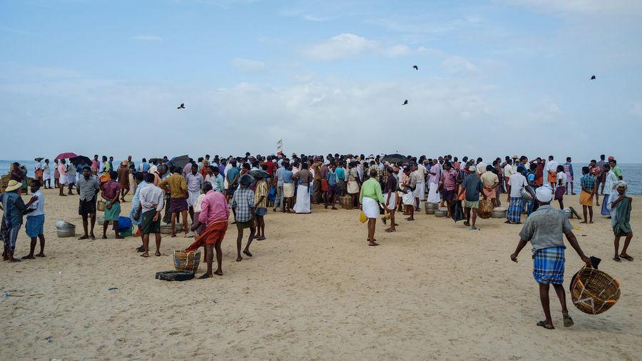 Fishermen Gathered At Beach Against Sky