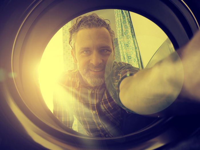 Close-up portrait of man seen through washing machine