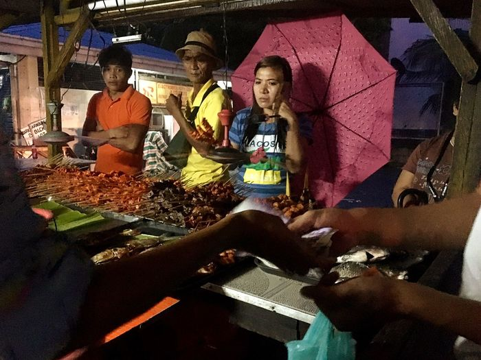 A man pays for his chicken intestine barbecue while others wait for their turn to buy at a barbecue/grill stall in Taguig, Metro Manila. The stall sells grilled fish and squid and a variety of barbecue items like chicken intestines, pigs ear, chicken feet, coagulated pig's blood, pork liver, pig's large intestine among others. Streetphotography EyeEm Best Shots Philippines Manila People Adult Barbecue Barbecue Stick Vendor Chicken Feet Chicken Intestine Grilled Fish