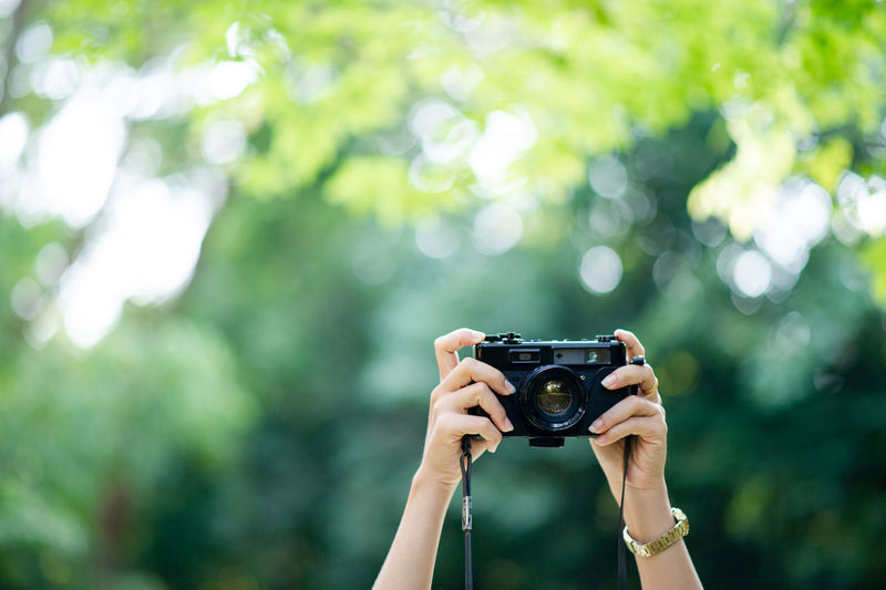 Cropped hand of woman holding camera against plants