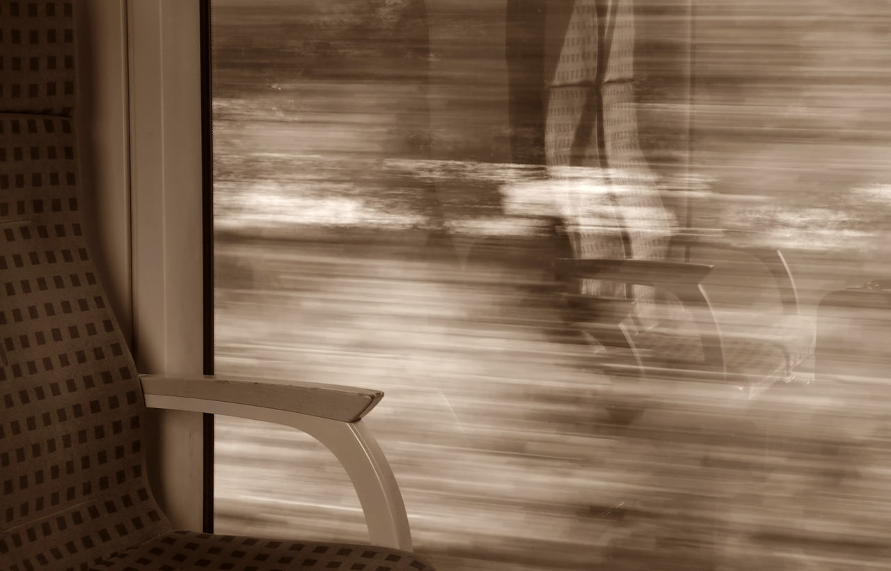 window, seat, no people, public transportation, indoors, train, train - vehicle, blurred motion, rail transportation, chair, glass - material, day, transparent, transportation, mode of transportation, reflection, architecture, motion