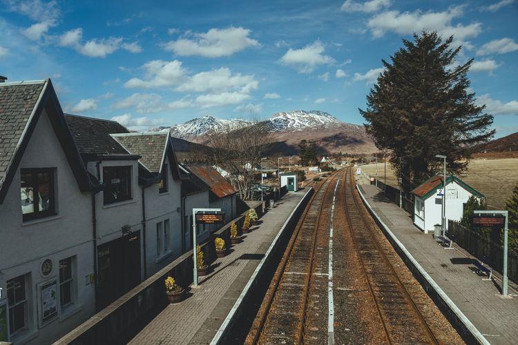 Railroad tracks amidst buildings against sky