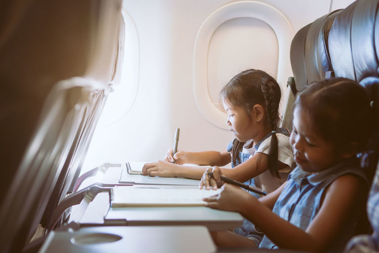 Activity Adorable Air Aircraft Airline Airplane Airport Asian  Book Chair Child Cute Daughter Departure Drawing Education Entertainment Family Flight Fly Friend Girl Happy Holiday Journey Kid Learn Leisure Magazine Paint Paper Passenger Plane Read Relaxation Safety Seat Sibling Sister Sitting Study Tourism Transport Transportation Travel Traveler Trip Vacation Window Write
