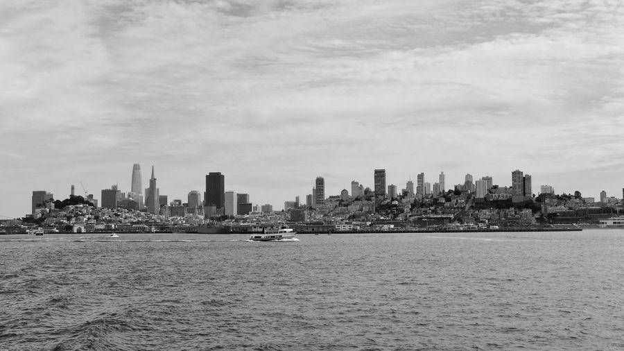 Sea by city buildings against sky