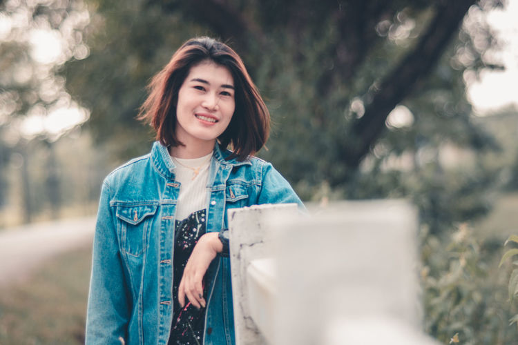 Asian Teenage Girl Asian Teen Beautiful Woman Beauty Casual Clothing Emotion Front View Hair Hairstyle Happiness Holding Looking At Camera One Person Portrait Smiling Standing Women Young Adult Young Women