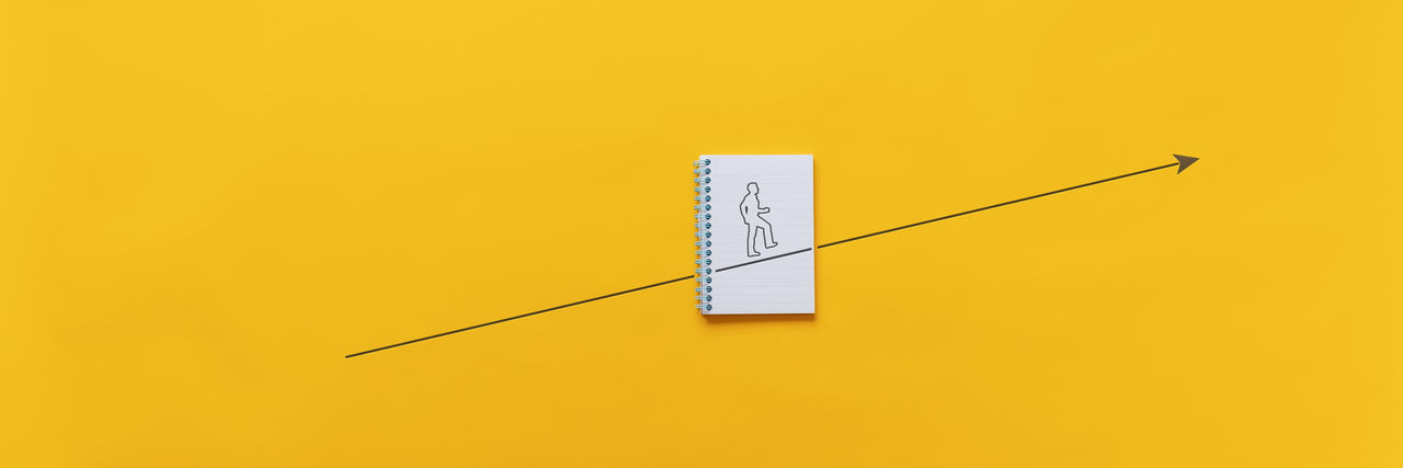 Close-up of clock on paper against yellow background