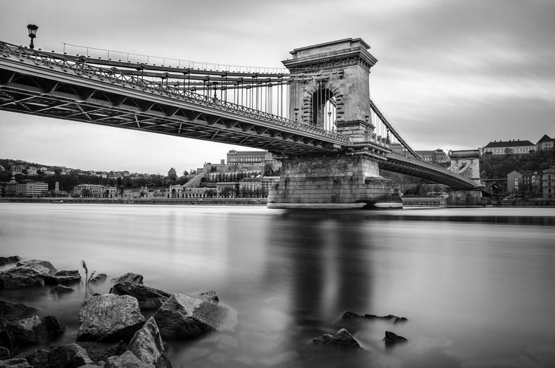 Low angle view of chain bridge over danube river against cloudy sky