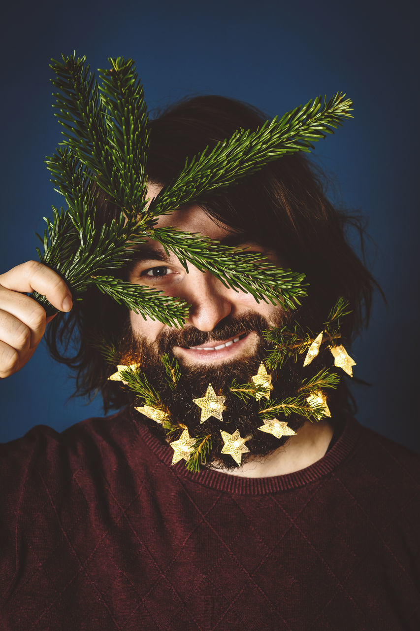 one person, real people, plant, front view, young adult, lifestyles, leisure activity, beard, nature, headshot, young men, portrait, holding, hairstyle, facial hair, hair, human body part, casual clothing, human face