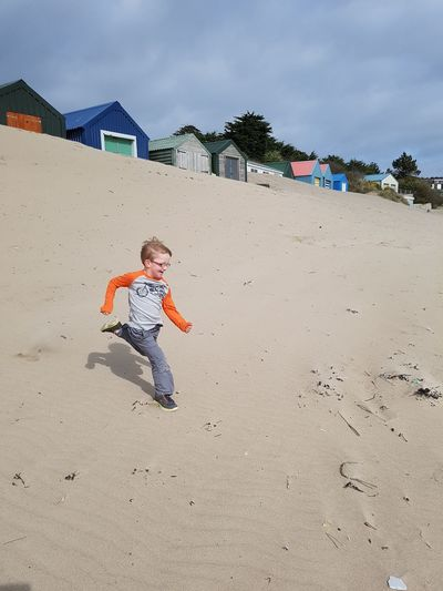 Sand Dune Boy Running Down Sand Dune Boy Running On Beach Boy Running Beach Huts Child Running Child Having Fun Sand Pail And Shovel Child Full Length Childhood Beach Boys Males  Sand Playing Summer