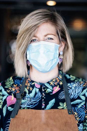 Portrait of a woman with apron wearing protective mask agains virus