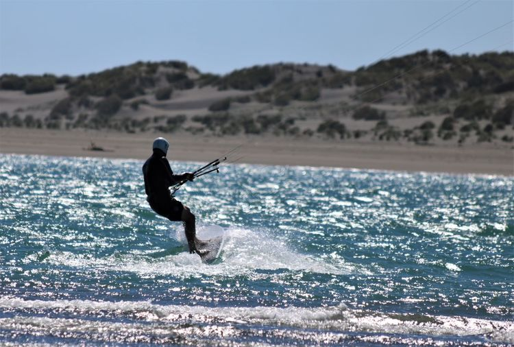 Side view of man kiteboarding on sea during sunny day