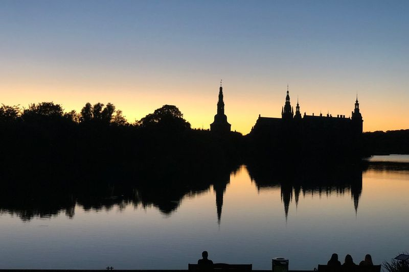 Silhouette of temple by lake during sunset