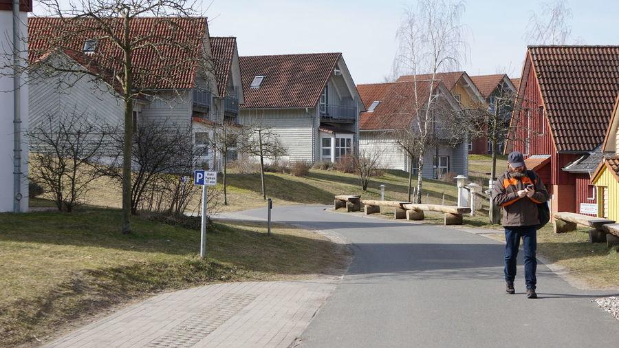 Man walking on road against buildings