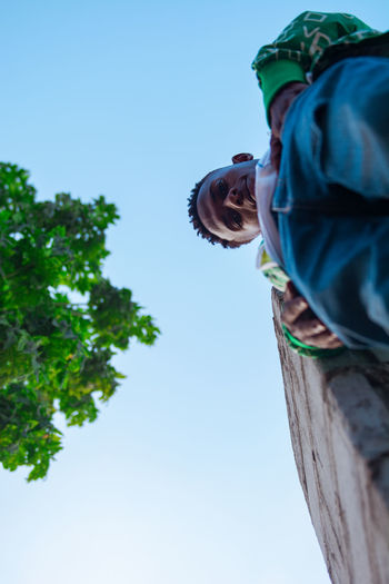 Low angle view of man against clear sky