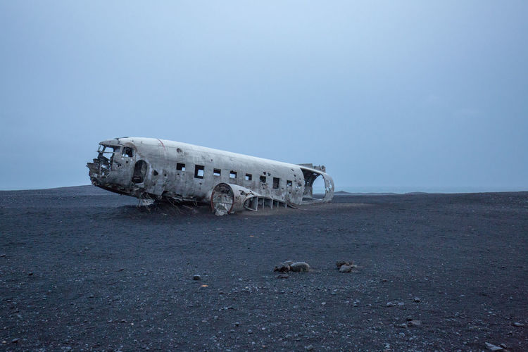 Abandoned airplane at beach against clear sky