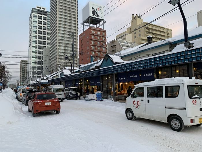 Cars on road by buildings in city during winter