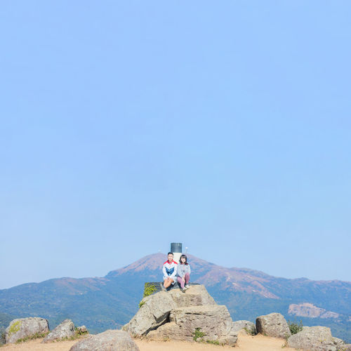 Man sitting on mountain against clear blue sky
