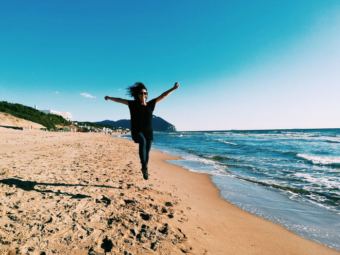 Jump Beach Beauty In Nature Clear Sky Day Energetic Full Length Horizon Over Water Leap Leisure Activity Lifestyles Nature One Person Outdoors Real People Sand Scenics Sea Shore Sky Standing Water Young Adult Young Women