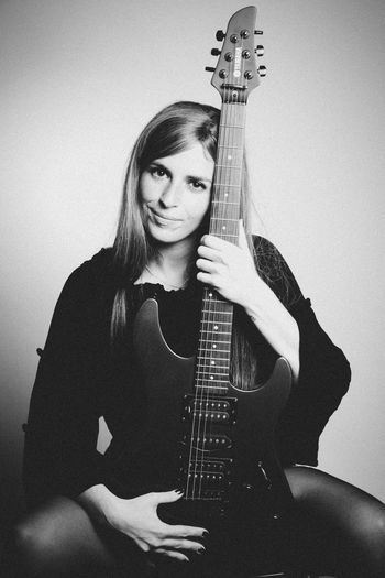 Portrait of girl on black and white Music Musical Instrument String Instrument Guitar Musical Equipment Arts Culture And Entertainment One Person Young Adult Portrait Indoors  Holding Front View Looking At Camera Real People Artist Playing Musician Waist Up Electric Guitar Hairstyle Plucking An Instrument Bass Guitar
