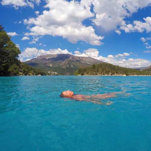 Woman swimming in turquoise sea against mountains