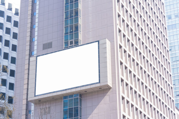 Low angle view of blank billboard on building in city