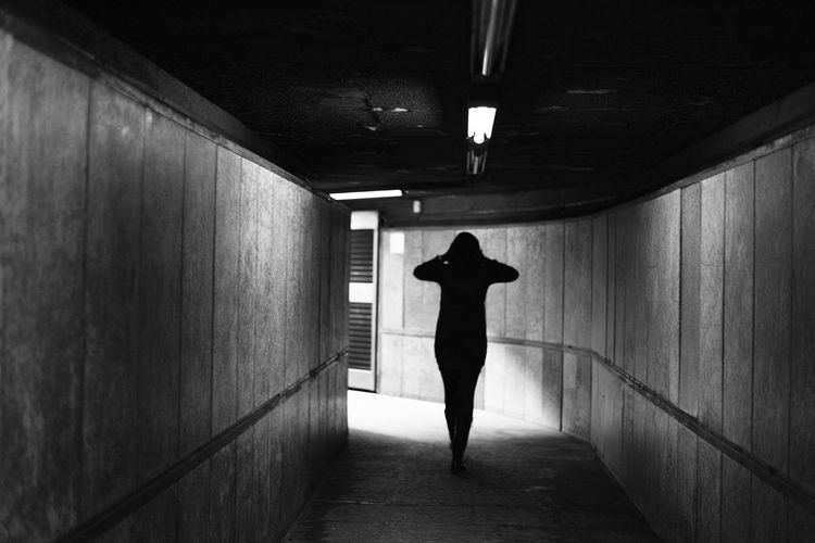 Rear view of woman standing in dark corridor