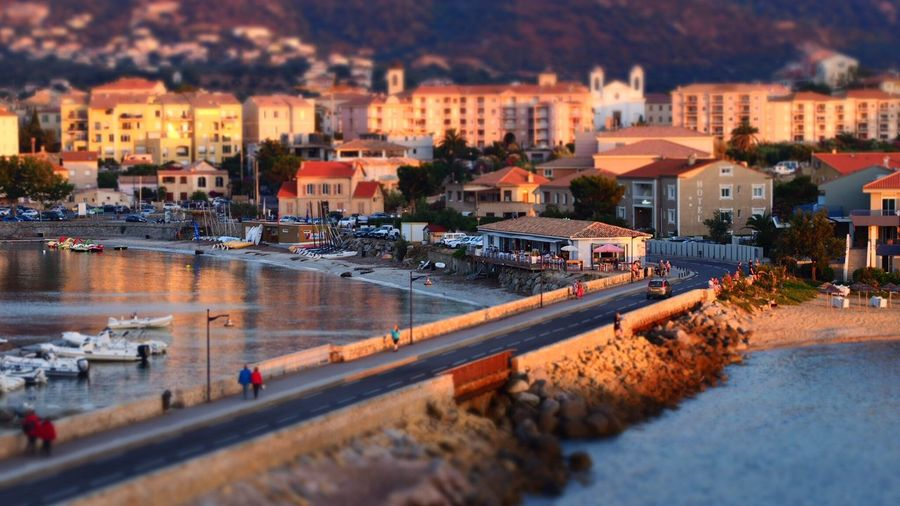 Tilt-shift image of people walking on road amidst sea