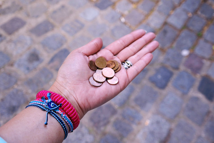 Cropped hand holding coins over footpath