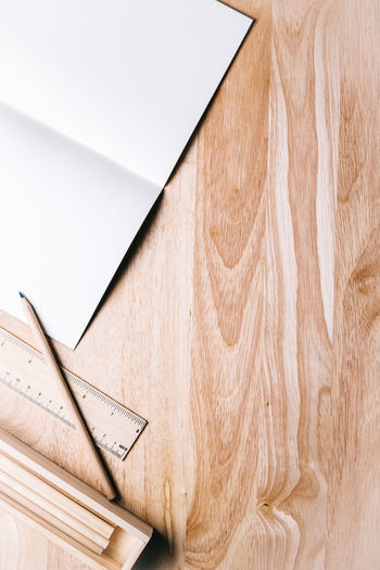 High angle view of book and pencil on wooden table