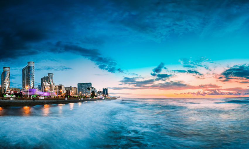 Sea by illuminated buildings against sky during sunset