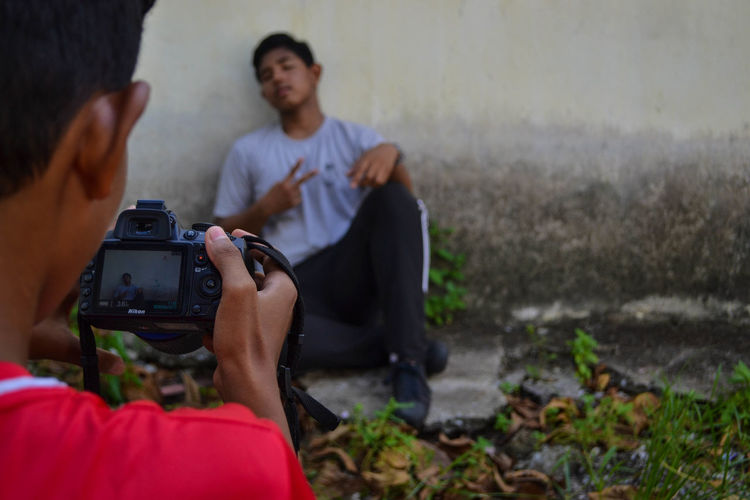 Rear View Of Teenage Boy Photographing Friend Sitting Against Wall