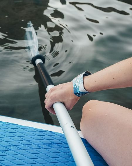 Midsection of woman holding oar at lake