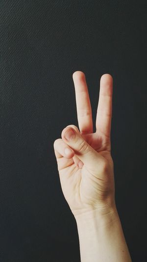 Cropped image of person showing peace sign against wall
