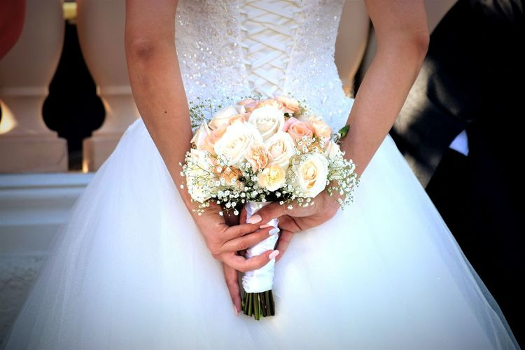 Midsection of bride holding rose bouquet