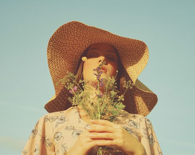Portrait of woman with bouquet wearing hat against blue sky