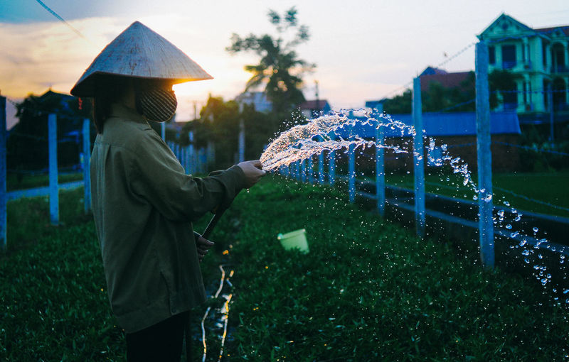 Side view of female farmer spraying water at farm during sunset