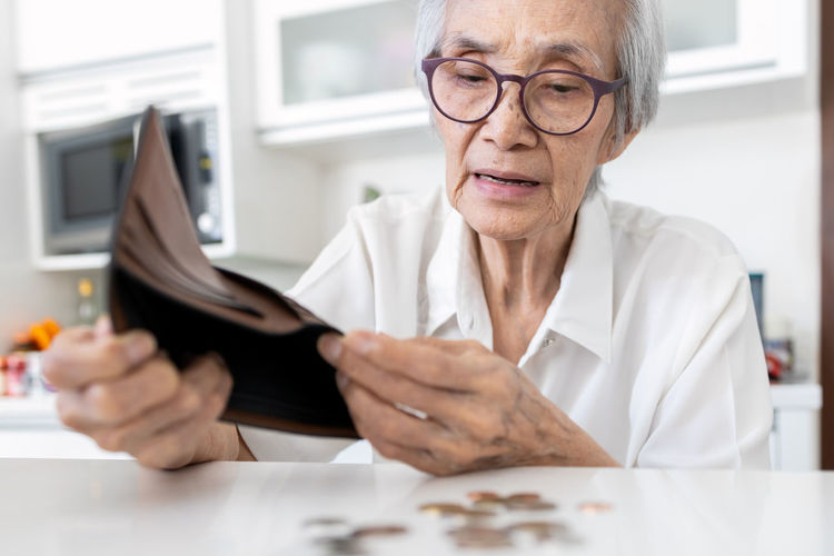 Close-up of senior woman removing coins from wallet on table