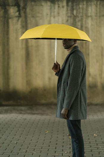 Woman holding umbrella standing on wet street