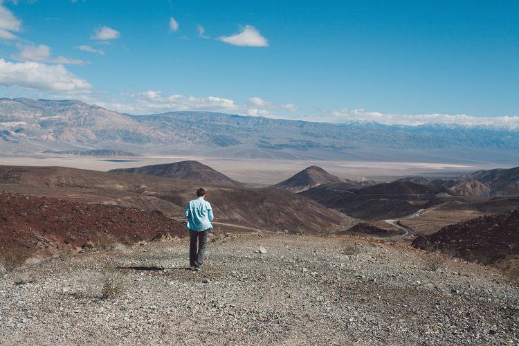 Man standing on arid landscape against sky